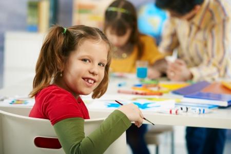 salle classe: Portrait d'enfant d'�ge du primaire heureuse assis � son bureau regardant la cam�ra dans la classe d'art dans la classe de l'�cole primaire, en souriant. Banque d'images