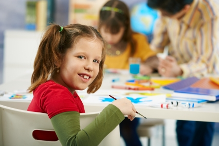 class rooms: Portrait of happy elementary age child sitting at desk looking at camera in art class in primary school classroom, smiling.