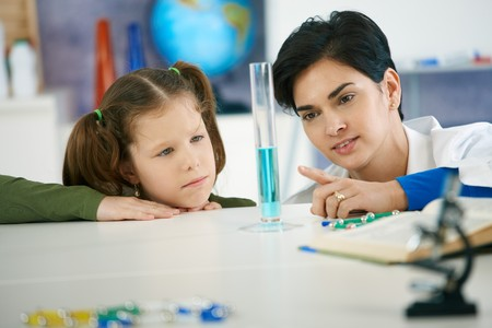 elementary age girls: Pupil and teacher looking at test tube in chemisty class at elementary school. Teacher explaining.