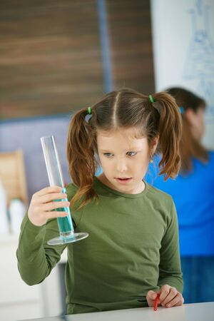 Elementary age school girl looking at test tube in science class at primary school. photo