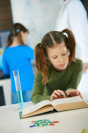 chemistry class: Elementary age schoolgirl looking at book in science class in primary school classroom.