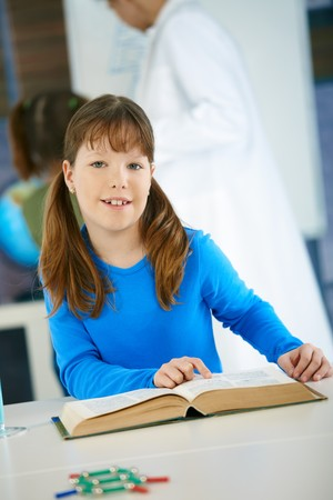 Elementary age schoolgirl looking at book in science class in primary school classroom. photo