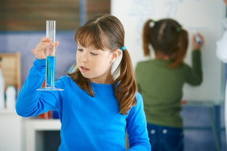 chemistry class: Elementary age school girl looking at test tube in science class at primary school.