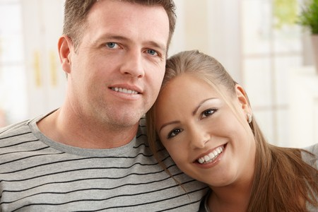 Portrait of happy couple at home, smiling woman leaning on mans shoulder. photo