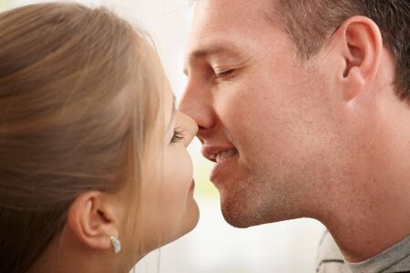 Smiling man about to kiss woman with eyes closed in closeup. photo
