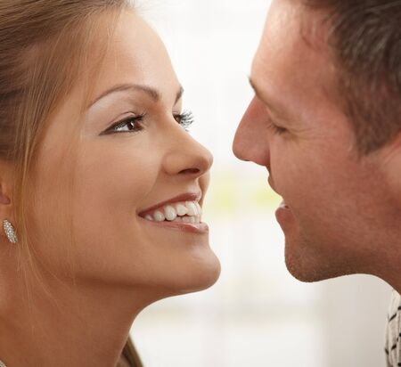 Smiling happy couple looking at each other before kissing in closeup. photo