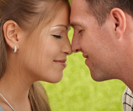 hand on forehead: Loving couples faces in closeup, foreheads touched, facing each other, smiling. Stock Photo