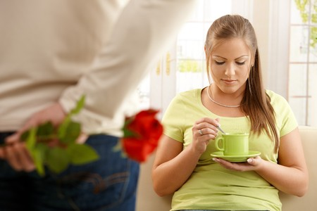 Man giving red rose to woman, hiding flower behind his back, woman looking down at tea cup sitting on sofa. photo
