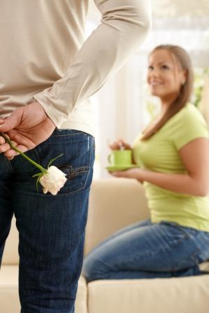 mujer con rosas: Hombre en la clandestinidad de enfoque elev� detr�s de espalda, mujer arrodillada sobre el sof� con taza de t� en la mano buscando al hombre.  Foto de archivo