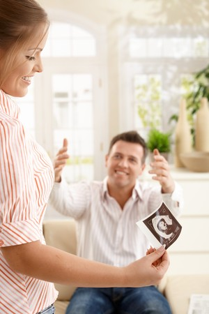 Smiling mother looking at ultrasound image of baby, sitting father raising arms to hug sitting on sofa. photo