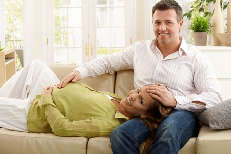 Portrait of expecting parents smiling happily together on couch in living room. photo