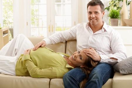 two stroke: Retrato de esperando los padres felizmente sonriendo juntos en sof� en sala de estar.