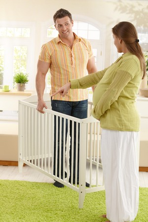 Pregnant mother pointing at right place of baby bed in living room, smiling father holding bed. photo