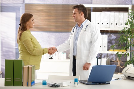 Smiling pregnant woman shaking hands with doctor in consulting room. photo