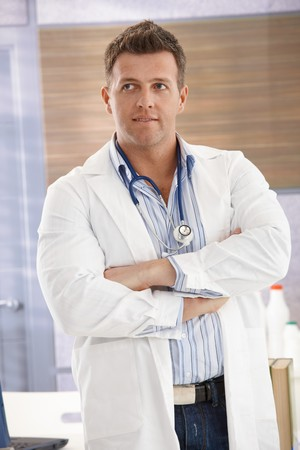 smock: Handsome mid-adult doctor standing in white smock arms folded in consulting room.