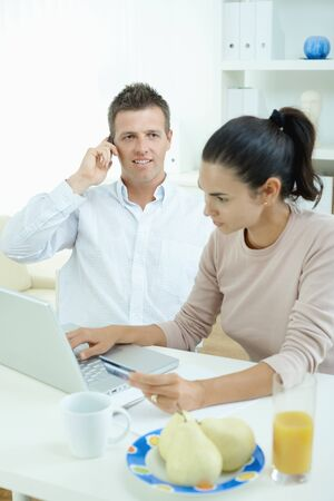 Young couple sitting at desk shopping on internet from home. Calling phone, using laptopcomputer and paying with credit card. Stock Photo - 7488038