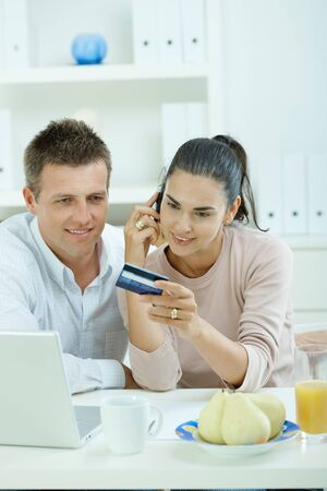 Young couple sitting at desk shopping on internet from home. Calling phone, using laptopcomputer and paying with credit card. photo