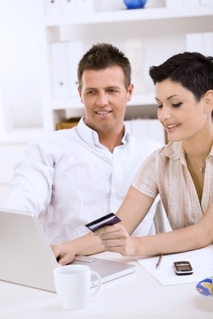 Happy young couple paying with credit card at home. Stock Photo - 7488021