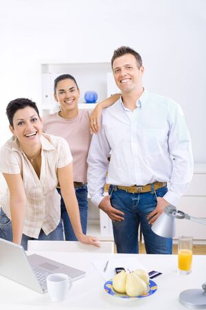 collaborating: Happy team of office workers running small business, smiling. Stock Photo