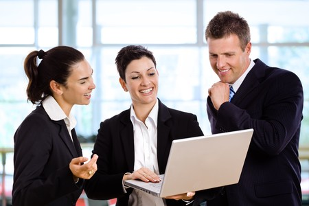 Three happy businesspeople standing and talking in office lobby, holding laptop computer in hand. photo