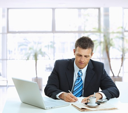 Businessman sitting at table in office lobby, writing note on paper. photo