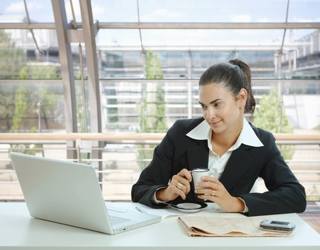 Businesswoman sitting at table in office lobby, drinking coffee and using laptop computer. photo