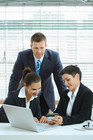 Young businesspeople talking in office lobby, looking at smart mobile phone, smiling. Stock Photo - 7488035