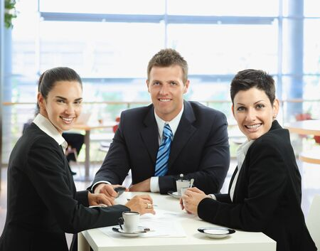 Happy young business people talking on meeting at coffee table, smiling. photo