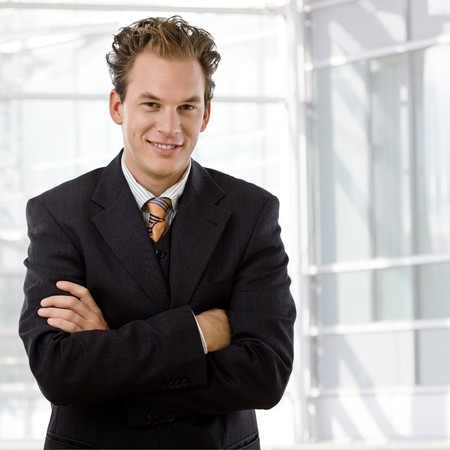 Portrait of happy young businessman smiling at office. photo