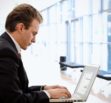 look pleased: Businessman working on laptop computer at office lobby.