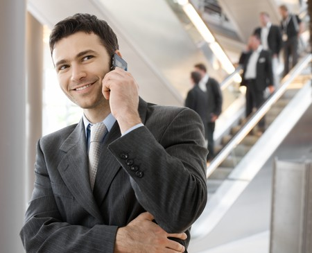 businessman waiting call: Young smiling businessman calling on phone at office.