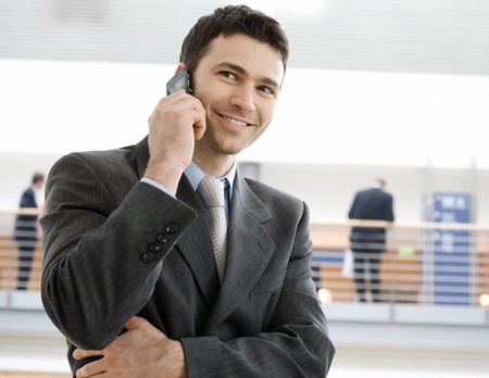 Young smiling businessman calling on phone at office. Stock Photo - 7488036