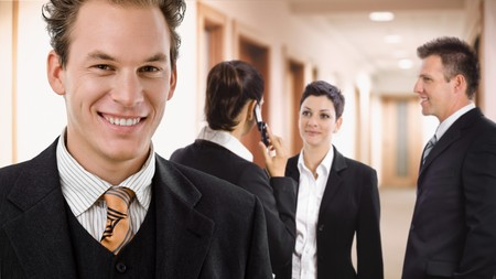 Happy businessman smiling in front, other businesspeople talking in the background. photo