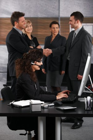 executive assistants: Young businesswoman sitting at desk in corporate office, talking on headset. Businessmen shaking hands in the background. Stock Photo