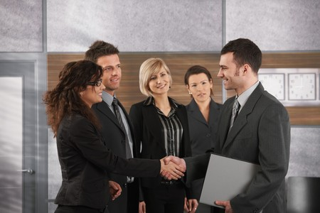Happy businessman introducing himself to business team in office. Stock Photo - 7520474