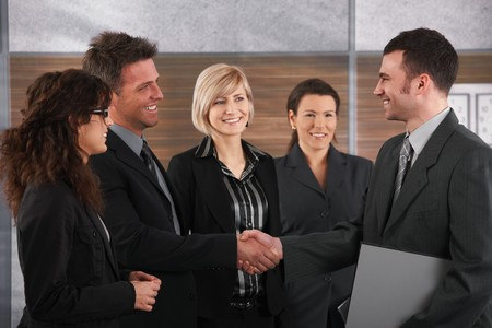 Happy business partners shaking hands in meeting room, smiling. photo