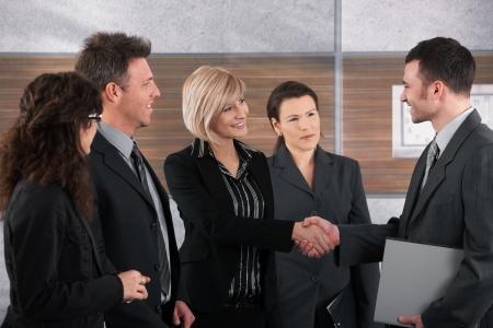 dandose la mano: Empresario sonriente y empresaria agitando las manos en la Oficina.