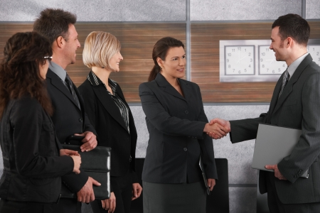 Smiling businessman and businesswoman shaking hands in office. photo