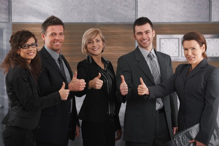 Portrait of happy businesspeople standing in office showing OK sign, smiling. photo