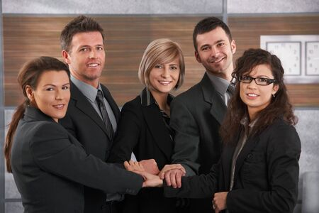Team portrait of happy businesspeople standing in office with joined hands, smiling. Stock Photo - 7520469
