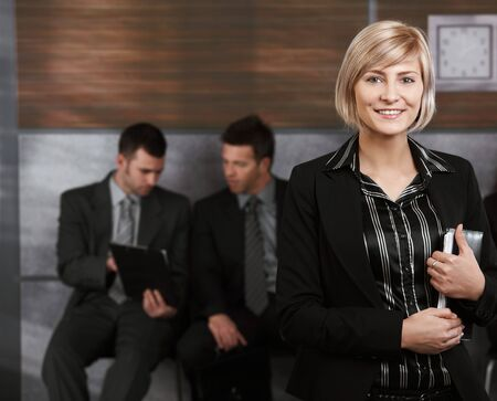 Happy young businesswoman standing in office hallway, holding personal organizer, smiling. photo