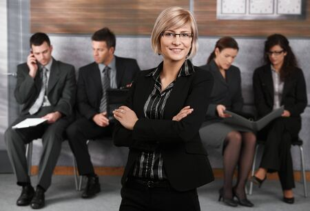 Portrait of confident young businesswoman standing in office hallway, arms crossed, smiling. Stock Photo - 7520433