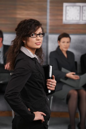 Portrait of confident young businesswoman standing in office with hand on her hip, looking back. photo