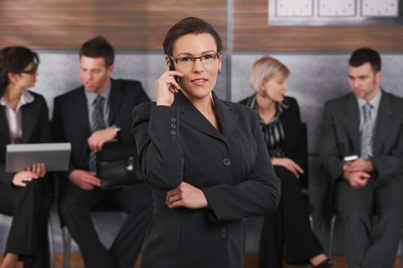 Portrait of happy businesswoman standing in office lobby, talking on mobile phone, smiling. Stock Photo - 7520444