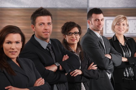 Portrait of business team standing in a row with arms crossed, smiling. photo