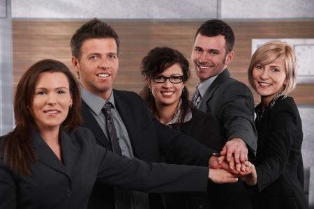 Portrait de gens heureuses debout dans un bureau avec les mains jointes, sourire.