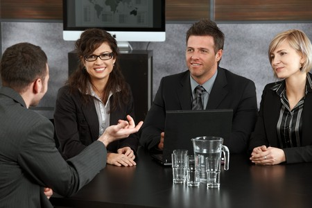 Young applicant explaining to panel of happy businesspeople during job interview in office. photo