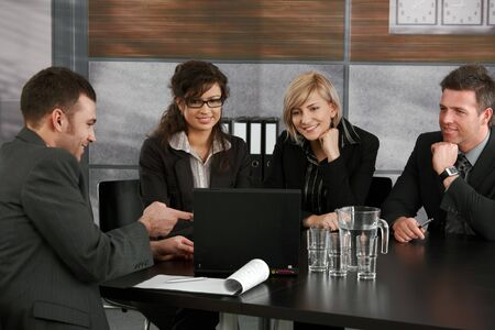 Young businesspeople having a meeting at table in office. Businessman showing data on laptop computer, others looking at screen, smiling. photo