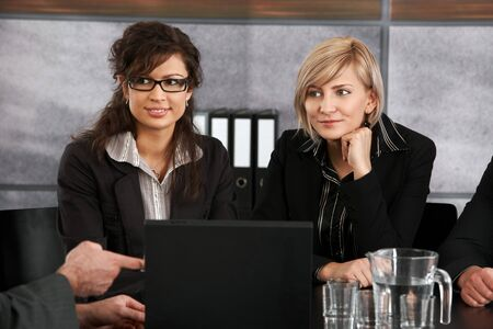 Two businesswomen sitting at meeting table, looking to businessman out of picture, smiling. photo