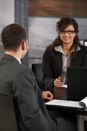 Happy young female candidate smiling to businessman during job interview. photo